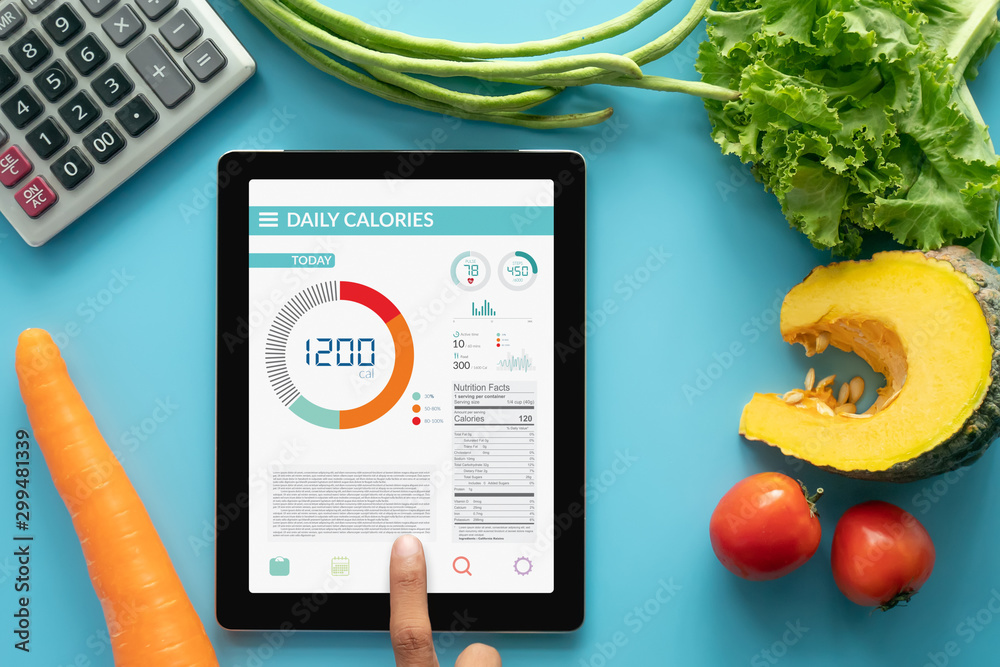 Fototapety, obrazy: Calories counting , diet , food control and weight loss concept. woman using Calorie counter application on tablet at dining table with fresh vegetable and calculator