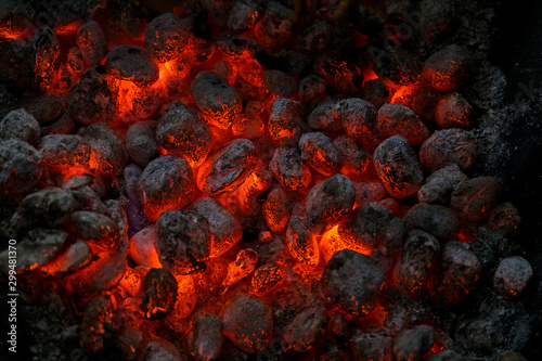 Fotomural Coals of a bonfire burning at night .