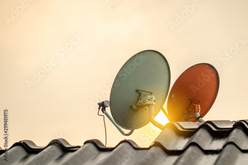 The satellite dishes on the roof for digital TV reciever with the sun light flare in the afternoon or evening Obraz na płótnie