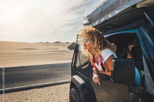 Beautiful blonde curly hair adult young woman outside the car enjoying the travel lifestyle and alternatie vacation with tent on the roof and free camping everywhere - people traveling - desert - 299485763