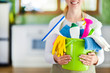canvas print picture - Woman holding cleaning items in plastic bucket. Kitchen service washing concept.