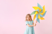 Cute Little Girl With Paper Windmill On Color Background