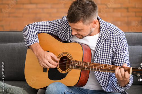 Handsome man playing guitar at home - 299492583