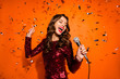canvas print picture - Portrait of charming pop start girl have karaoke party on her prom sing song hold microphone enjoy loud music wear maroon outfit isolated over orange color background confetti falling
