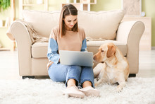 Beautiful Young Woman With Cute Dog Using Laptop At Home