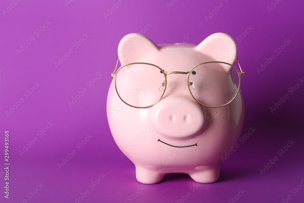 Fototapety, obrazy: Piggy bank with eyeglasses on color background