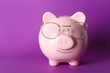canvas print picture - Piggy bank with eyeglasses on color background