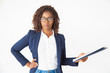 Leinwanddruck Bild - Serious confident leader holding documents, keeping hand on hip, looking at camera. Young African American business woman standing isolated over white background. Female business leader concept