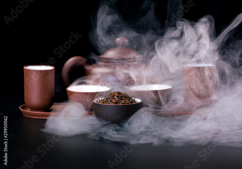 Recess Fitting Tea Asian tea ceremony. Clay teapot and tea cups with vapor on a black background.