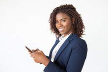 Smiling Successful Professional Using Mobile Phone, Texting Message. Young African American Business Woman Standing Isolated Over White Background. Communication Concept