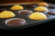 Freshly Baked Dark And Light Cupcake Cakes In A Muffin Tin, Background Goes To Black, Copy Space,