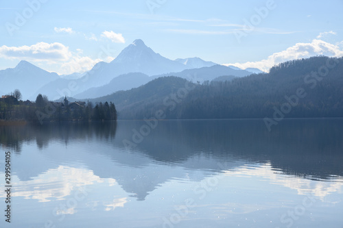 Leinwand Poster weissensee, idyllic lake in dusty morning light front of the blue mountains of t