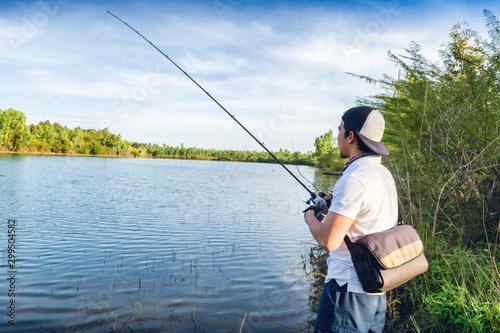 Fotobehang Vissen Man fishing in the lake at sunset.