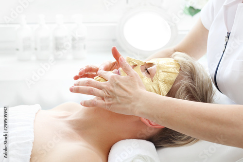 Collagen cosmetic mask with gold. Care treatment in a beauty salon. The beautician applies a golden mask to a woman's face. Beautiful woman in a beauty salon during facial treatment