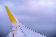 White And Yellow Wing Of A Plane With The Clouds