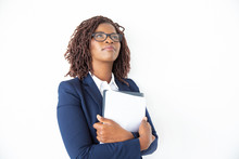 Pensive Office Assistant In Glasses Holding Papers, Looking Up. Young African American Business Woman Standing Isolated Over White Background. Advertising Concept