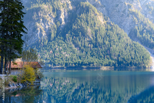 small boathouse at lake plansee in fall season between austrian alps mountains Wallpaper Mural