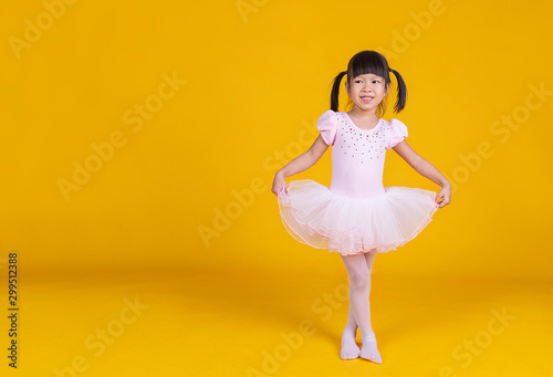 Portrait of little asian child girl dreams of becoming ballerina in a pink tutu skirt isolated on yellow background. Happy young girl practise her dance. Education childhood toddler lifestyle concept - 299512388