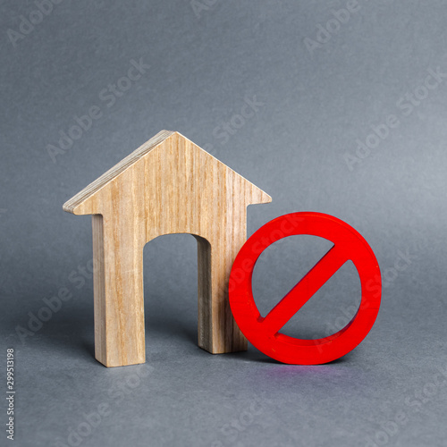 Fototapeta  Wooden house figurine and a red prohibition symbol NO