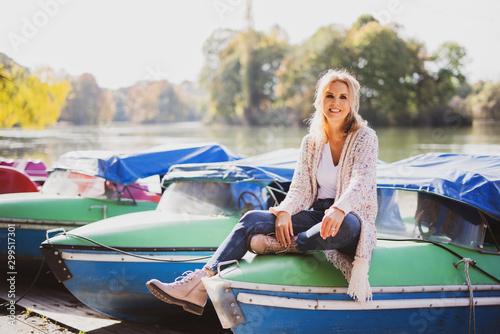 Fotomural  Ältere attraktive Frau sitzt auf einem Boot