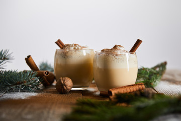 selective focus of eggnog cocktail with whipped cream near cinnamon sticks and spruce branches on wooden table isolated on grey