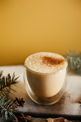 traditional eggnog cocktail with cinnamon near spruce branches and scattered sugar powder on orange background