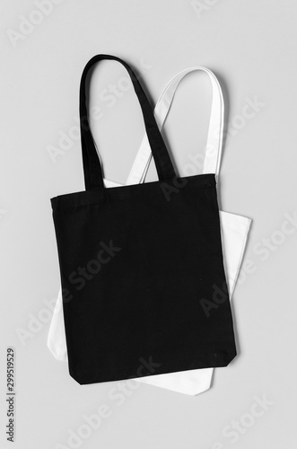 Fototapeta  Black and white tote bags mockup on a grey background.