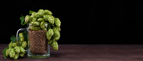 Home brewing concept. Mug with malt and fresh green of hops on dark wooden table. Black background. Empty space for text