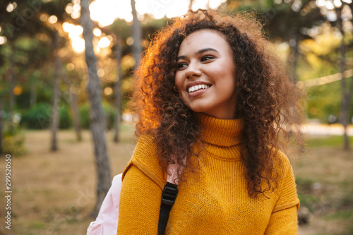 Fotomural  Happy optimistic young curly woman walking in park