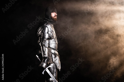 Fotografía handsome knight in armor holding sword on black background