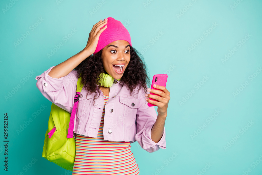 Fototapeta Photo of cheerful positive cute nice sweet casual omg rucksack bag girlfriend excited about reading perfect feedback from audiences in striped t-shirt pink jacket in headphones cap headwear isolated