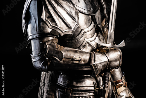 cropped view of knight in armor holding sword isolated on black Wallpaper Mural