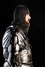 Side View Of Handsome Knight In Armor Isolated On Black