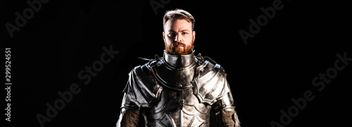 Foto panoramic shot of handsome knight in armor isolated on black