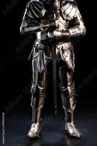 Fotomural cropped view of knight in armor holding sword on black background