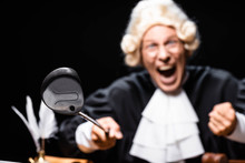 Selective Focus Of Angry Judge In Judicial Robe And Wig Holding Golf Club Isolated On Black