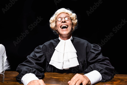 Fotomural smiling judge in judicial robe and wig sitting at table isolated on black
