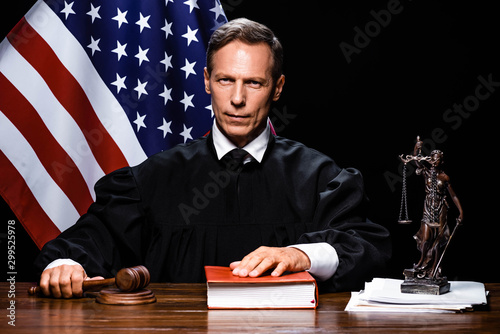 Photographie judge in judicial robe holding gavel and putting hand on book