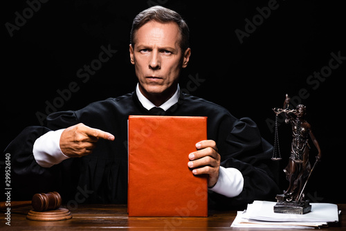 Canvas Print judge in judicial robe sitting at table and pointing with finger at orange book