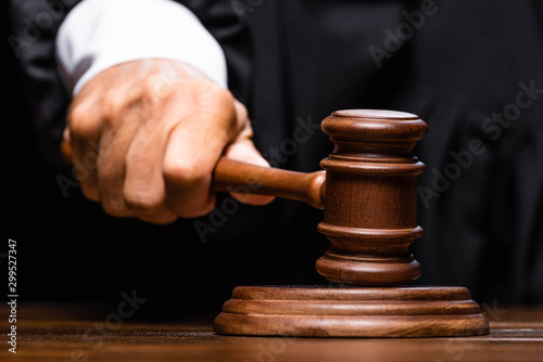 Photo sur Toile Amsterdam cropped view of judge in judicial robe sitting at table and hitting with gavel