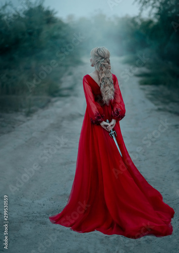 dangerous-blonde-queen-in-red-fashion-lush-dress-hides-a-dagger-behind-backdrop-dark-fantasy-forest-in-fog-concept-revenge-conspiracy-betrayal-halloween-party-turned-away-without-face-long-train