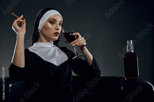 Photo Cropped half-turn shot of a nun, sitting on a chair