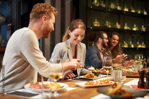 Obraz Handsome caucasian ginger taking food out of his girlfriend's plate while sitting in restaurant for dinner. In background are their friends. - fototapety do salonu