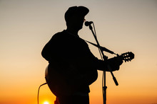 Silhouette Of A Man Playing Gu...