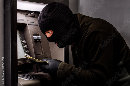 Fotomural thief with crowbar opens the ATM.