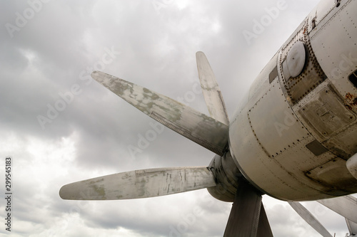 Obraz na płótnie Part of the fuselage of the old military plane with the propeller closeup against the background of an empty and gray sky