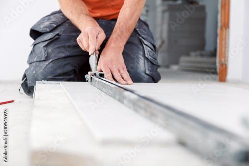 Photo Fliesenleger bei der Arbeit , handwerker schneidet fliesen mit schneidetisch we