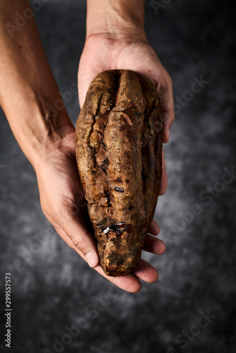 man with a roasted sweet potato in his hands