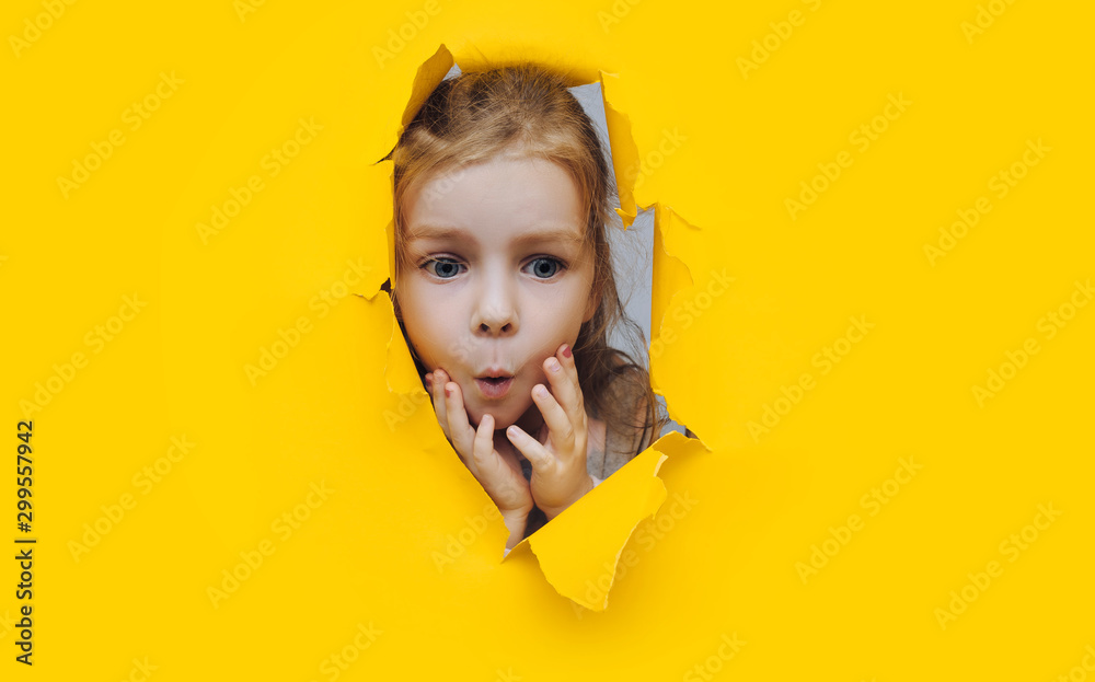 Fototapety, obrazy: Funny red-haired child girl peeping through hole on yellow paper. The concept of surprise, joyful mood from what he saw. Discounts, sales, surprise. Copy space.