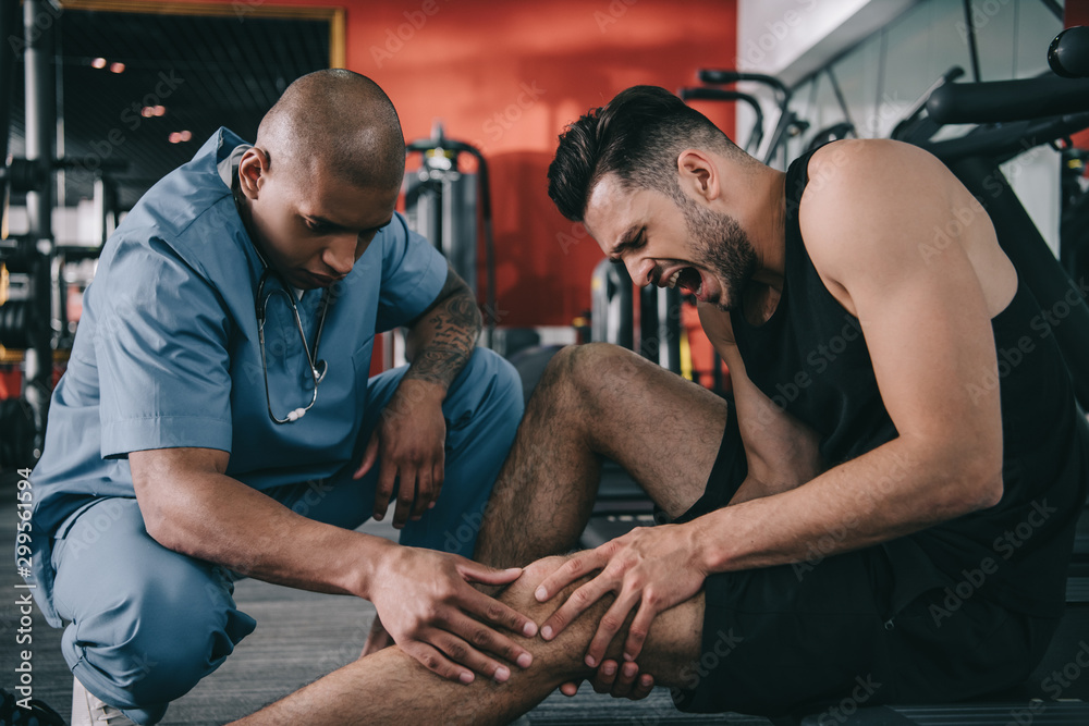 Fototapeta african american doctor examining injured knee of screaming sportsman